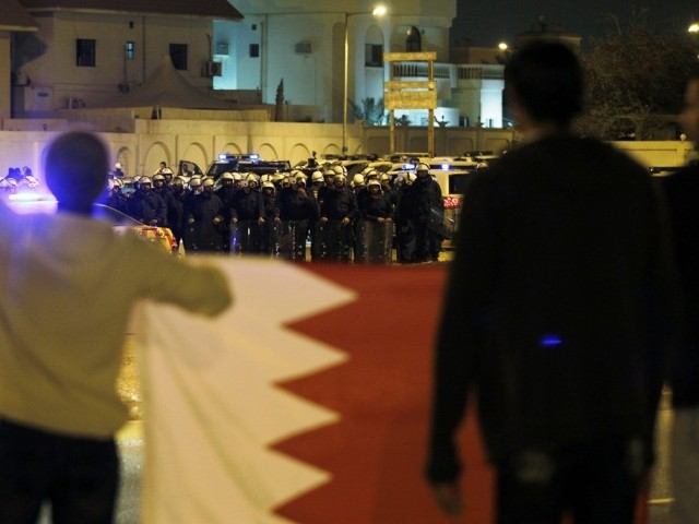 Residents hold a Bahraini flag in front of riot-police after a fight broke out between nationalised Sunni and Shiites in Hamad Town, south of Manama March 3, 2011. PHOTO: REUTERS