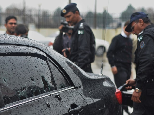 Police officials inspect the bullet-riddled car of Minorities Minister Shahbaz Bhatti following an attack in Islamabad on March 2, 2011. PHOTO: AFP