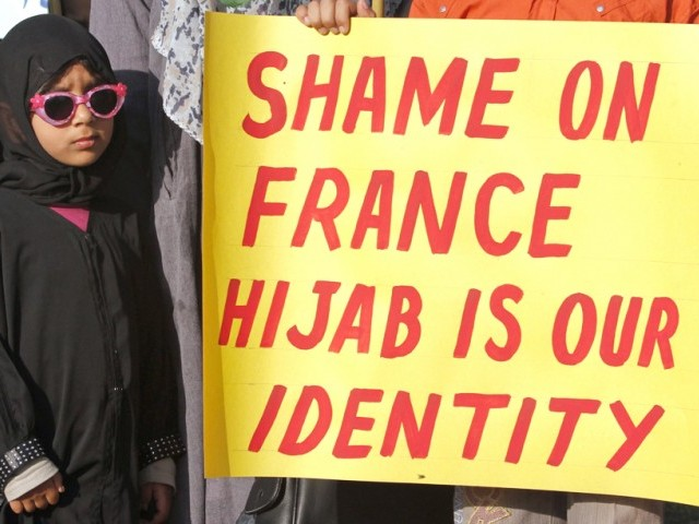 A child stands near a supporter of Pakistan's religious and political party Jamaat-e-Islami with a placard during a demonstration in Islamabad April 13, 2011, against the ban on full face veils in France. PHOTO : REUTERS