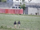 Pakistani policemen walk past a compound, surrounded in red fabric, where locals reported a firefight took place overnight in Abbotabad, located in Pakistan's Khyber Pakhtunkhwa province May 2, 2011. Al Qaeda leader Osama bin Laden was killed in a firefight with U.S. forces in Pakistan on Sunday, ending a nearly 10-year worldwide hunt for the mastermind of the Sept. 11 attacks. Obama said U.S. forces led a targeted operation that killed bin Laden in Abbotabad north of Islamabad. PHOTO:REUTERS