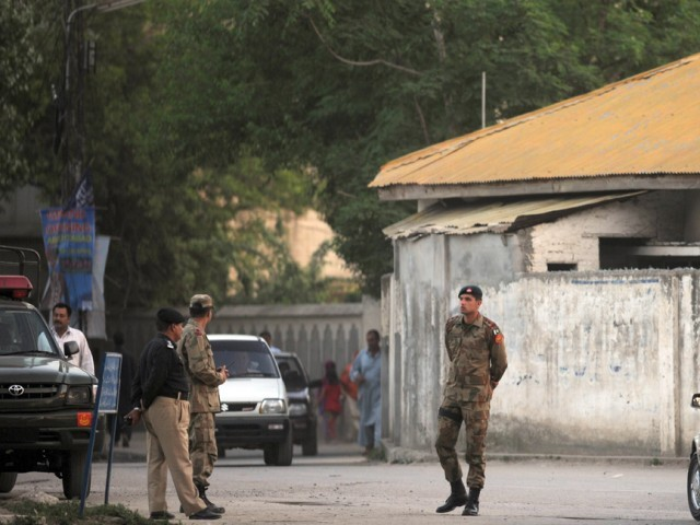 "Pakistani soldiers and police officials keep vigil near a building the hideout of Al-Qaeda leader Osama bin Laden after his death by US Special Forces in a ground operation in Abbottabad on May 2, 2011. Pakistan said that the killing of Osama bin Laden in a US operation was a ""major setback"" for terrorist organisations and a ""major victory"" in the country's fight against militancy. PHOTO: AFP"