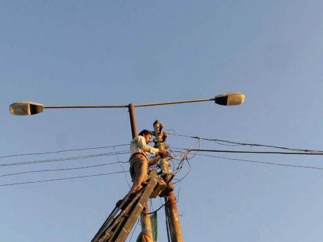A KESC worker fixing wires near Abdullah Shah Ghazi's shrine in November 2010. Two months later, KESC offered 4,500 such staffers a golden handshake in a bid to streamline operations. PHOTO: FILE