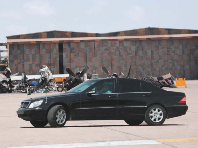 Prime Minister Yousaf Raza Gilani drives past the wreckage of the P3C-Orion aircraft at PNS Mehran. PHOTO: WIRES
