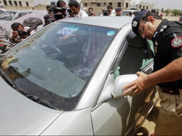 Policemen inspect a damaged car, currently parked in a police station, in which a Saudi diplomat was travelling in when under attack by gunmen, in Karachi May 16, 2011. REUTERS