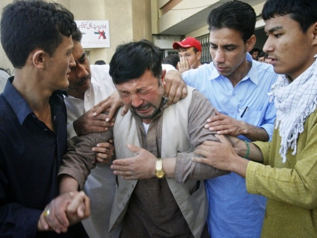 A man is comforted by community members, after he arrived to the local hospital in Quetta to find a family member shot dead. PHOTO: REUTERS