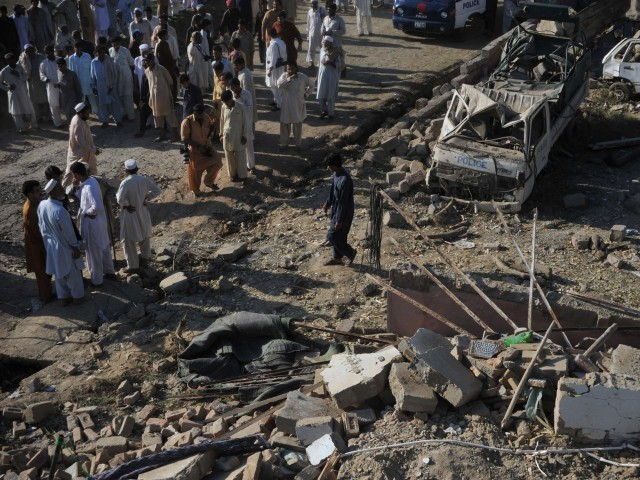 People look at the site of a bomb blast in Charsadda, about 53 kilometres west of Abbottabad on May 2, 2011. PHOTO: AFP