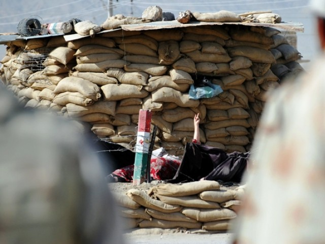 Woman attacker (C) raises her hand next to a security checkpoint during exchange of fire with Pakistani troops in Quetta. PHOTO: AFP