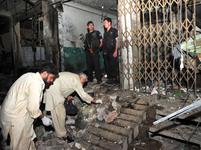Pakistani security officials examine the site following twin bomb blasts in Peshawar on June 11, 2011. Twin bomb blasts at a crowded supermarket killed at least 34 people and injured more than 80 in Pakistan's northwestern city of Peshawar late on June 11, police said. PHOTO:AFP