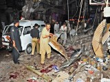 Pakistani people remove debris as they search for blast victims at the site of twin bomb blasts in Peshawar on June 11, 2011. Twin bomb blasts at a crowded supermarket killed at least 34 people and injured more than 80 in Pakistan's northwestern city of Peshawar late on June 11, police said. PHOTO:AFP