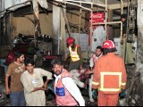 Pakistani volunteers remove a blast victim at the site of twin bomb blasts in Peshawar on June 11, 2011. Twin bomb blasts at a crowded supermarket killed at least 34 people and injured more than 80 in Pakistan's northwestern city of Peshawar late on June 11, police said. PHOTO:AFP