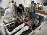 Pakistani paramedics treat injured bomb blast victims at a hospital in Peshawar on June 12, 2011. Twin bomb blasts at a crowded supermarket killed at least 34 people and injured more than 80 in Pakistan's northwestern city of Peshawar late on June 11, police said. PHOTO:AFP