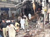 Pakistani police and volunteers search for blast victims at the site of twin bomb blasts in Peshawar on June 11, 2011. Twin bomb blasts at a crowded supermarket killed at least 34 people and injured more than 80 in Pakistan's northwestern city of Peshawar late on June 11, police said. PHOTO:AFP