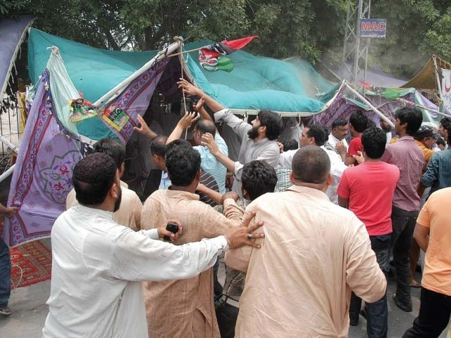 Activists of a political party tearing up the election office of another political party in Muzaffarabad. PHOTO: EXPRESS