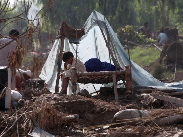 A boy sits on a bed as his family members salvage belongings from their destroyed house in Pabbi. PHOTO: REUTERS/FILE