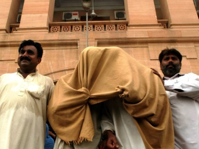 Arrested Pakistani paramilitary Rangers and a civilian, their faces covered in blankets, sit in a armored vehicle as they leave for jail from an anti-terrorism court after a hearing in Karachi. PHOTO: FILE/AFP