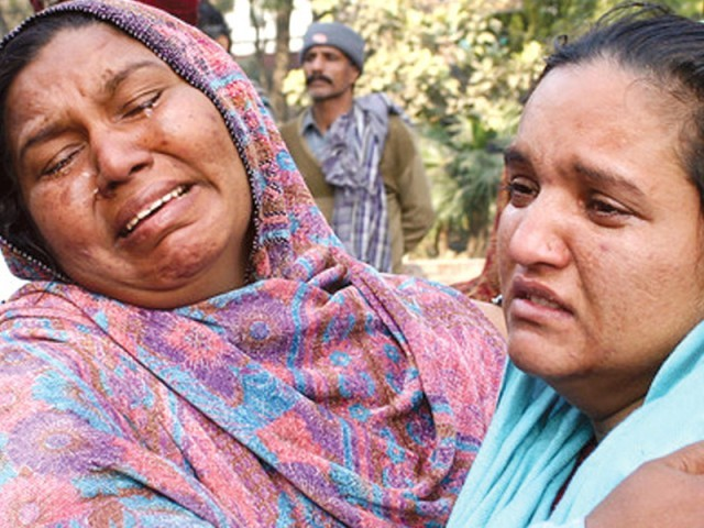 Rioters in Gojra ran amok over rumours of desecration of the Holy Quran. A woman consoles another who is grieving for the loss of one of her relatives. PHOTO: FILE