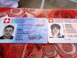 The Swiss identity card of Oliver David Och (L) and the Swiss driving licence of Daniela Wildmer are set on a table at a police station in Quetta. PHOTO: AFP