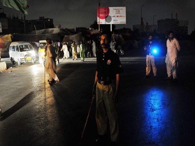 Pakistani policemen stand guard in the middle of a road in a tense area of Karachi on June 14, 2011. A fresh wave of violence blamed on political and ethnic tensions killed at least 12 people in Pakistan's biggest city of Karachi overnight, officials said. Tensions are high between the Muttahida Qaumi Movement (MQM) and the Awami National Party (ANP), which represent different ethnic communities and straddle volatile political fault lines. Killings have been blamed on their loyalists. PHOTO: AFP