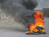 A man rides a motorcycle through the smoke of tyres burnt by angry protesters against target killing in Karachi July 8, 2011. PHOTO: REUTERS