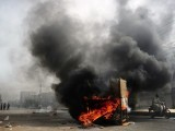 A Pakistani motorcyclist rides past a pile of burning tyres and furniture in a violence-hit western neighbourhood of Karachi on July 8, 2011.  PHOTO: AFP
