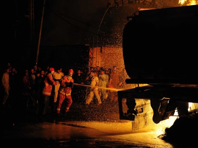 Firefighters try to control the fire started by the attack of a NATO oil tanker, as residents gather around, near a market in the suburb of Peshawar, on late July 16, 2011.  PHOTO: AFP
