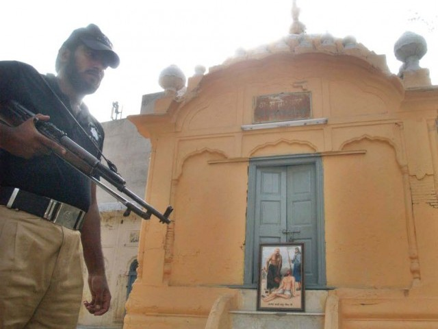 A policeman stands guard at a Sikh temple that a group claims is the burial site of a Muslim saint. PHOTO: ABDUL MANAN