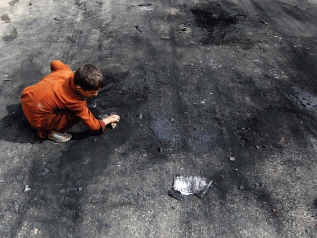 A child searches for scrap metal outside Afroze Textile in Ahsanabad where up to 80 parked staff motorcycles were set ablaze a day ago. PHOTO: ATHAR KHAN/EXPRESS
