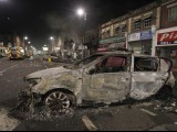 A burnt police car is seen on a street in Tottenham, north London August 7, 2011. PHOTO: REUTERS