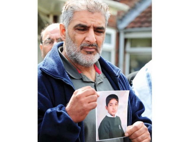 Haroon Jahan's father holds a picture of his son near the scene in Birmingham where Haroon and two other men were hit by a car and killed on Wednesday. PHOTO: AFP