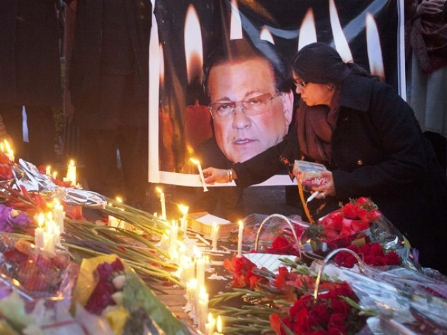 A woman lights a candle next to an image of the governor of Punjab Salmaan Taseer during a candlelight vigil in commemoration of Taseer, near the site of his assassination a day earlier, in Islamabad January 5, 2011. PHOTO: REUTERS/FILE