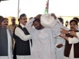 Prime Minister Yousuf Raza Gilani gives a bag of relief goods to a flood affectee in Tando Muhammad Khan. PHOTO: NNI