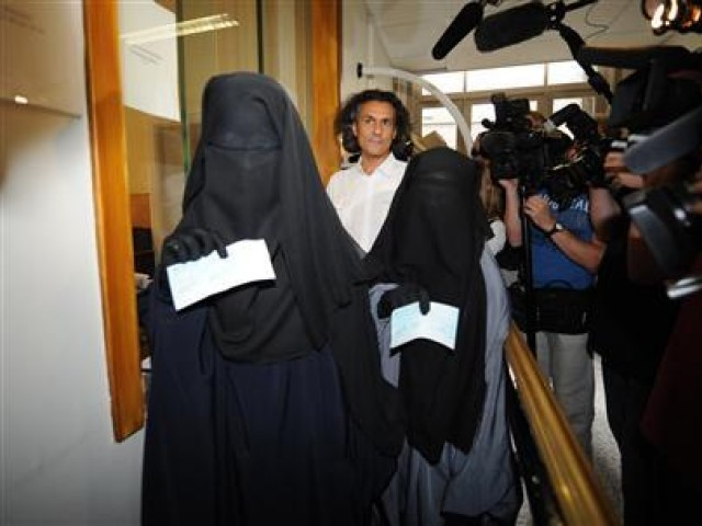 French businessman Rachid Nekkaz (C), who is said to be a candidate for the 2012 France's presidential election, stands next to Halima (L) and Imen (R) after he paid their fines for wearing a niqab in Brussels August 17, 2011. PHOTO: Reuters