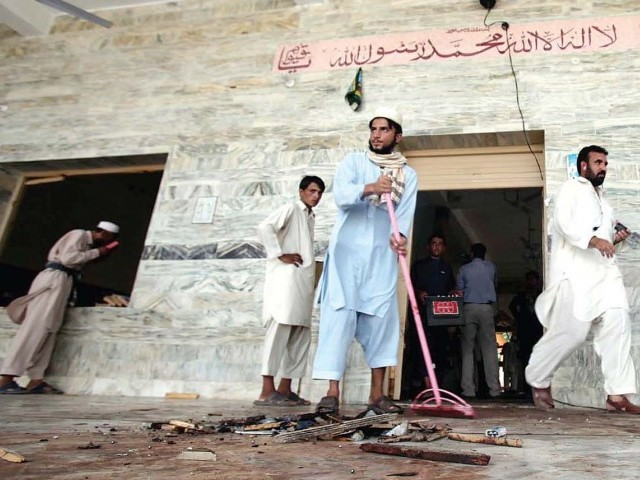 Local residents clean the mosque after the suicide attack in Jamrud. PHOTO: AFP