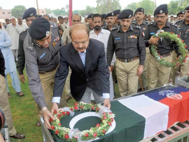 Sindh Home Minister Manzoor Wassan laying a wreath on the coffin of one of the four policemen who were shot dead in the attack on the police bus in Korangi on Saturday. PHOTO: MOHAMMAD AZEEM/EXPRESS