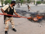 Paramilitary soldiers extinguish a fire set by protesters during a strike against recent politically-motivated killings in Karachi on August 23, 2011. PHOTO: AFP