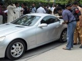 Security official collect evidence from the vehicle of Shahbaz Taseer at the site where he was kidnapped by unidentified men in Lahore on August 26, 2011. PHOTO: AFP