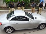 Police stand next to the car of the abducted son of slain former governor Salman Taseer in Lahore on August 26, 2011. PHOTO: AFP