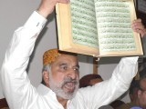 Zulfiqar Mirza raises the Holy Quran during a press conference at the Hyderabad Press Club. PHOTO: INP
