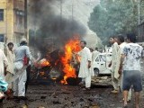 Local residents gather at the site of a car bomb blast in Quetta on August 31, 2011. A car bomb on August 31 killed at least four people and wounded 10 others in the restive southwestern Pakistani city of Quetta, police said. PHOTO: AFP