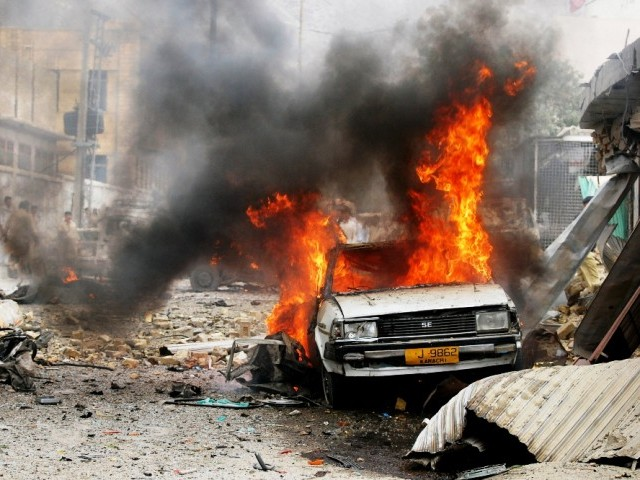 Local residents gather at the site of a car bomb blast in Quetta on August 31, 2011. A car bomb exploded in a parking lot after Eid prayers on August 31 killing at least four people adn wounding 10 others in the restive southwestern Pakistani city of Quetta, police said. PHOTO: AFP