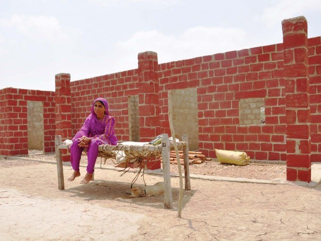 A woman awaits the completion of her new UNDP-provided house in Mazoor Village, Thatta. The plan is to build 198 houses - 25 are ready. PHOTO: UNDP PAKISTAN