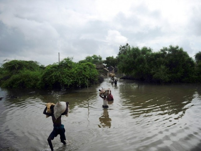 Villagers carry their belongings through flood water following heavy monsoon rain at Golarchi town in Badin district, about 200 km east of Karachi,  on September 13, 2011. PHOTO: AFP