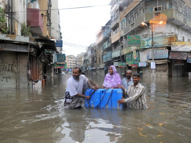 Relatives of a sick woman transport her atop a plastic tank to a hospital in Sadar on Tuesday morning. 100mm of rain flooded parts of Karachi. PHOTO : MOHAMMAD SAQIB/EXPRESS