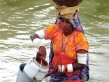 A villager salvages her cooking utensils through the flood water following heavy monsoon rain at Golarchi town in Badin district, about 200km east of Karachi, on Tuesday. PHOTO: AFP
