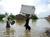 Villagers carry their belongings through of failing to invest in prevention measures after floods last year floodwater in Golarchi. The crisis came just weeks after aid agency Oxfam accused the government hit 21 million people and cost the economy $10 billion in the country's worst natural disaster. PHOTO: AFP