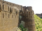 The outer wall and bastions of the fort with the merlon-shaped battlements which are equipped with loopholes to pour molten lead or oil onto besieging forces.