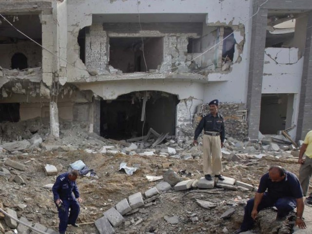 Policemen search through the crater left by the blast. PHOTO: REUTERS