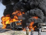 Pakistani local residents watch burning NATO supply trucks after they were attacked by armed militants on the outskirts of Quetta on September 27, 2011. PHOTO: AFP