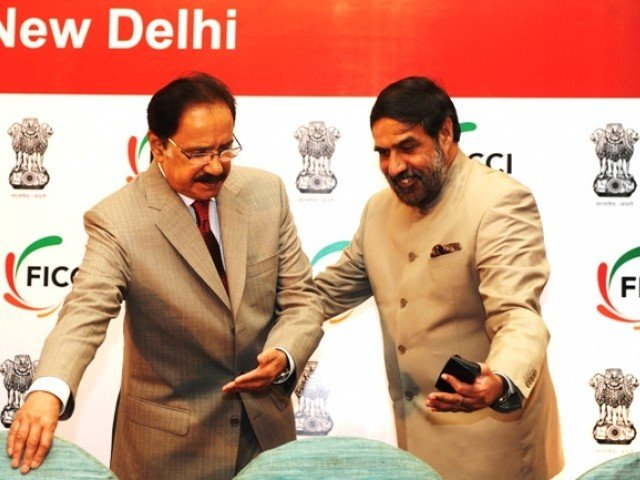 Indian Commerce Minister Anand Sharma (R) welcome his Pakistan counterpart, Makhdoom Amin Fahim, during an India-Pakistan Business Conclave, exploring business between neighbours in New Delhi on September 29, 2011. PHOTO: AFP
