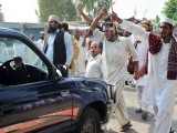 Supporters of Mumtaz Qadri, shout slogans as they stop the progress of a police vehicle during a protest after the court announced the death sentence for Qadri, outside Adiyala Prison in Rawalpindi on October 1, 2011. PHOTO: AFP